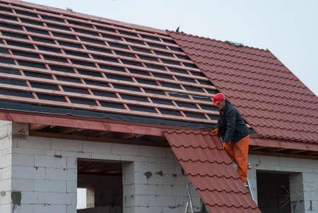 Builder assembles roof tiles of metal