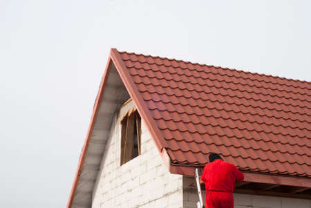 modular home: builder performs installation gable roof tiles of metal