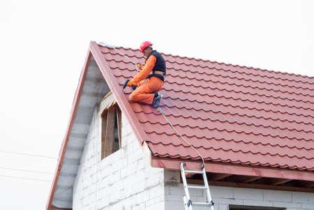 bouwer voert installatie zadeldak tegels van metaal Stockfoto