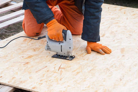 construction jigsaw to cut a sheet of plywood OSB