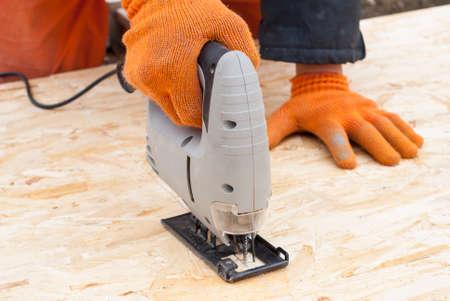 osb: construction jigsaw to cut a sheet of plywood OSB