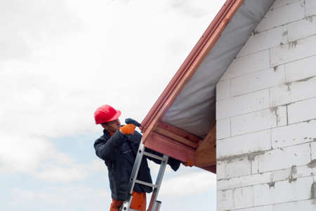 sheathing: builder performs installation gable roof tiles of metal
