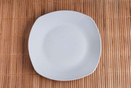 grunge cutlery: empty white plate on a bamboo table cloth background