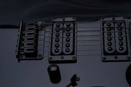 pickups: strings and pickups on the black electric guitar Stock Photo
