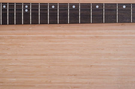 frets: electric guitar fretboard on a wooden background texture