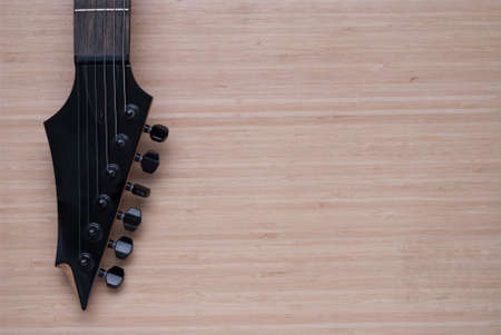 fretboard: electric guitar fretboard on a wooden background texture