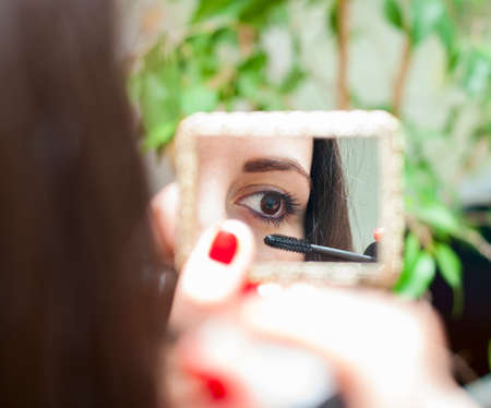 young woman paints the lashes mascara while looking in the mirror 免版税图像