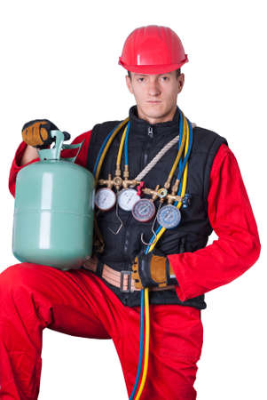 hands in the air: young man in work clothes holding a bottle with Freon Stock Photo