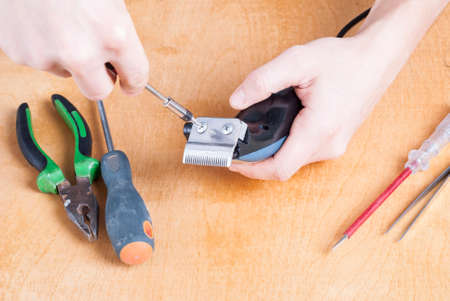 shearer: repairman with screwdriver on the table parsed shearer