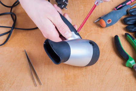 installer: repairman with screwdriver on the table parsed hairdryer