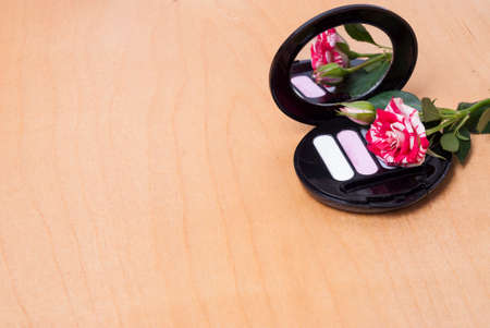 feminine background: womens cosmetics and rose on the table