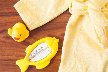 rubber ducky: thermometer, rubber ducky and a childrens bathrobe on the table