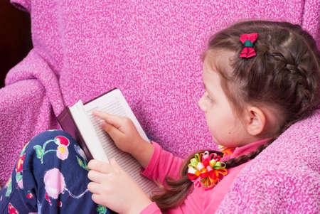 jolie petite fille: fille assise dans un fauteuil et de lire un livre