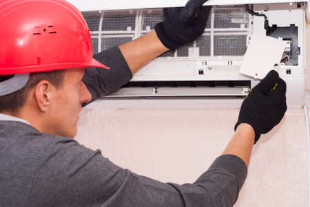 specialist cleans and repairs the wall air conditioner 스톡 콘텐츠