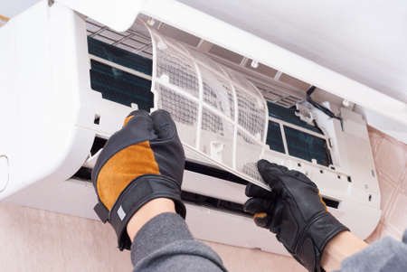 specialist cleans and repairs the wall air conditioner Foto de archivo