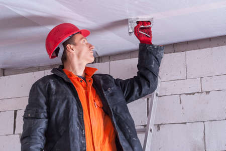 wooden beams: builder attaches vapor barrier to wooden beams on the ceiling Stock Photo