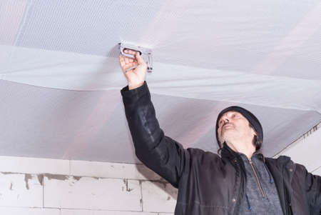 wood ceiling: builder attaches vapor barrier to wooden beams on the ceiling Stock Photo