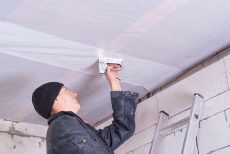 attaches: builder attaches vapor barrier to wooden beams on the ceiling Stock Photo