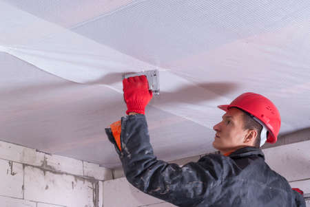 in ceiling: builder attaches vapor barrier to wooden beams on the ceiling Stock Photo