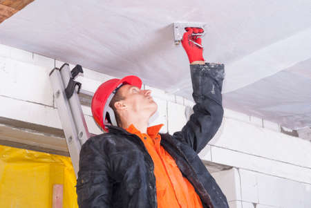 wooden ceiling: builder attaches vapor barrier to wooden beams on the ceiling Stock Photo