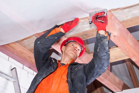 builder attaches vapor barrier to wooden beams on the ceiling Stock Photo