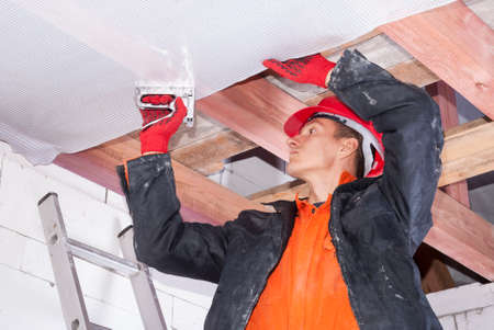 builder attaches vapor barrier to wooden beams on the ceiling Stockfoto
