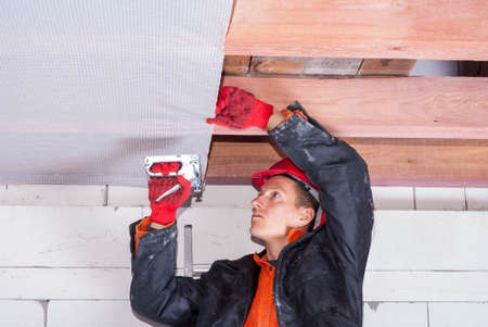 builder attaches vapor barrier to wooden beams on the ceiling 免版税图像
