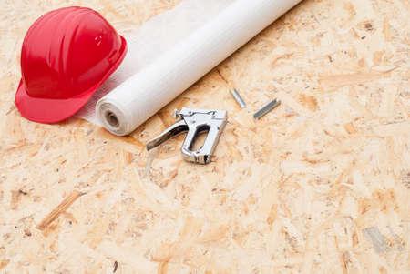 caulk: roll a vapor barrier, helmet and a stapler in the background OSB Stock Photo