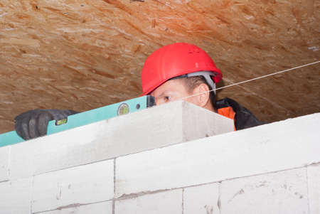 work gloves: bricklayer puts a wall of aerated concrete blocks Stock Photo