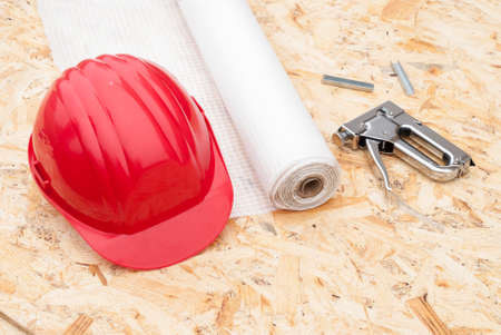 osb: roll a vapor barrier, helmet and a stapler in the background OSB Stock Photo