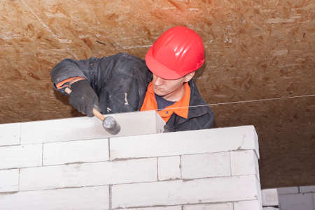 aerated: bricklayer puts a wall of aerated concrete blocks Stock Photo
