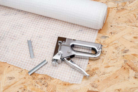 caulk: roll a vapor barrier and a stapler in the background OSB