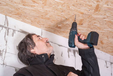 osb: builder twists the screw in the OSB sheet on the ceiling