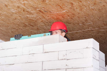 aligning: bricklayer puts a wall of aerated concrete blocks Stock Photo