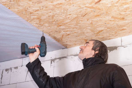 builder twists the screw in the OSB sheet on the ceiling