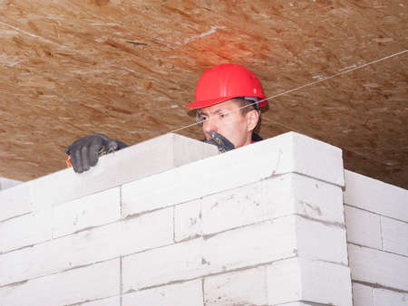 concrete blocks: bricklayer puts a wall of aerated concrete blocks Stock Photo