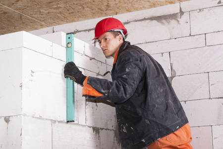 bricklayer: bricklayer puts a wall of aerated concrete blocks Stock Photo