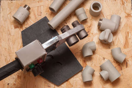 osb: polypropylene pipes, fittings and welding machine in the background OSB