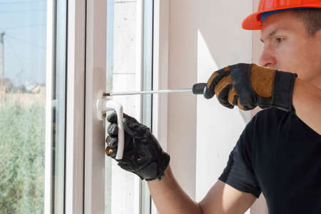 master with a screwdriver sets fittings on the window Foto de archivo