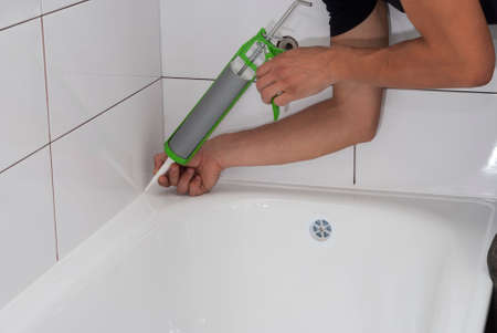 sealant: plumber apply silicone sealant to the joint bathtubs and ceramic tile