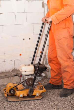 vibrating: builder with vibratory plates seals the base for pouring concrete