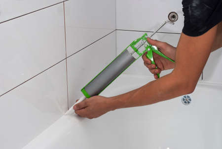 hermetic: plumber apply silicone sealant to the joint bathtubs and ceramic tile