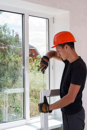master with a screwdriver sets fittings on the window Stockfoto