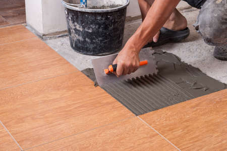 master puts on the floor adhesive for tiling Banque d'images