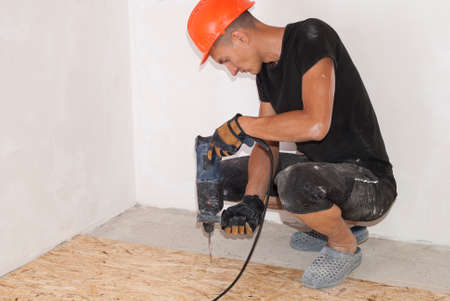 worker with hammer drill a hole in the floor