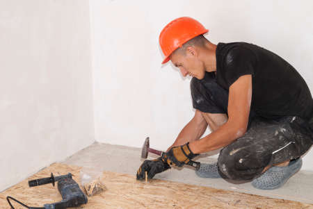 dowel: working hammers dowel into the hole on the floor Stock Photo