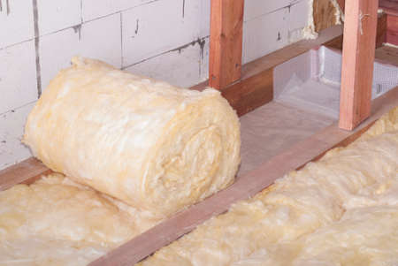 Rotolo di isolamento di lana minerale nel piano sottotetto Archivio Fotografico - 66760188