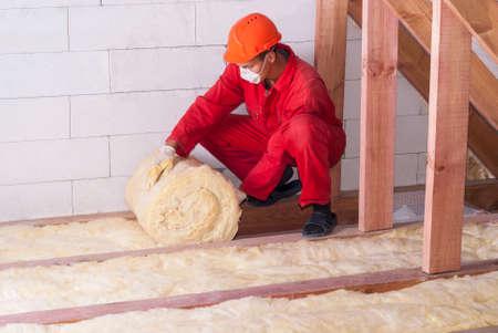 werkende isoleert de zolder met minerale wol Stockfoto