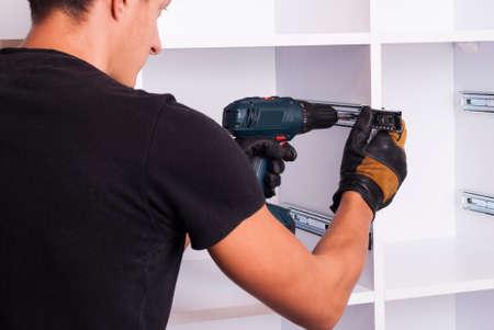 furniture maker sets telescopic rails on the cabinet Stockfoto