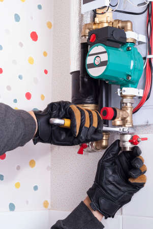 plumber installs household wall electric heating boiler 免版税图像